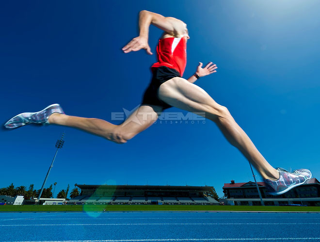 Athlete running around track.